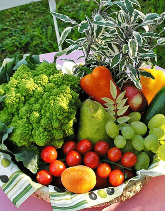 A basket of fiber rich foods such as apples, grapes, broccoli, and peppers