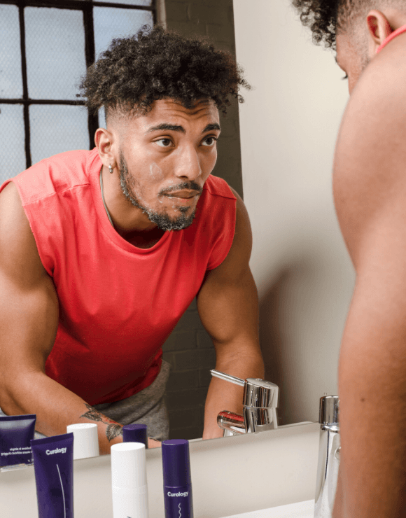 fit male looks into mirror washing his face