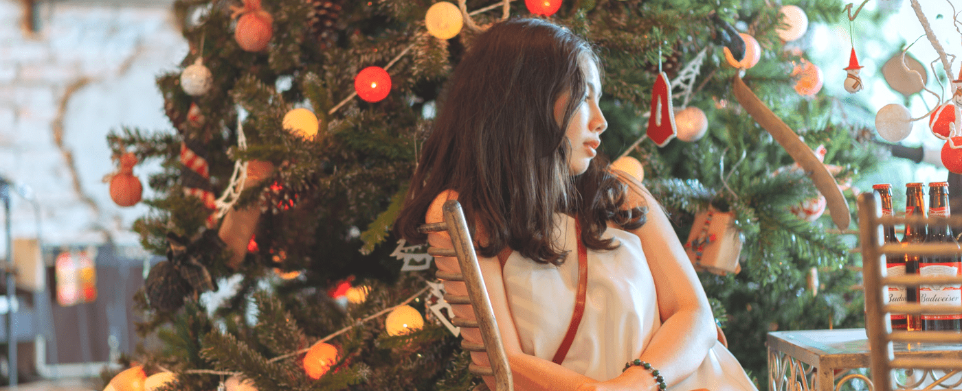 Young girl sitting in front of Christmas tree looking sad being away from home for the holidays