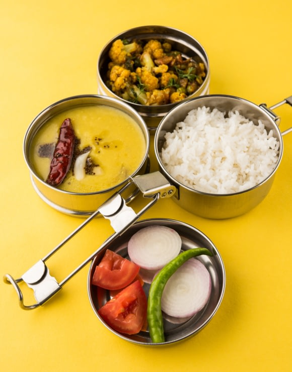 Pots and pans filled with Indian Tiffin Lunch including rice, curry, and vegetables