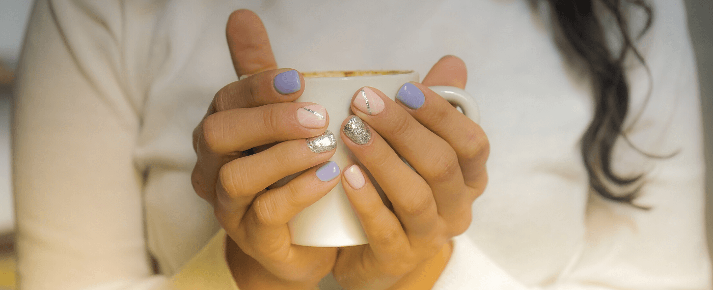 Girl showing off trendy nail colors and patterns while holding a coffee mug