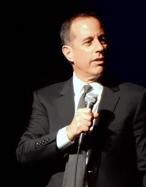 Jerry Seinfeld holding a microphone while giving a speech