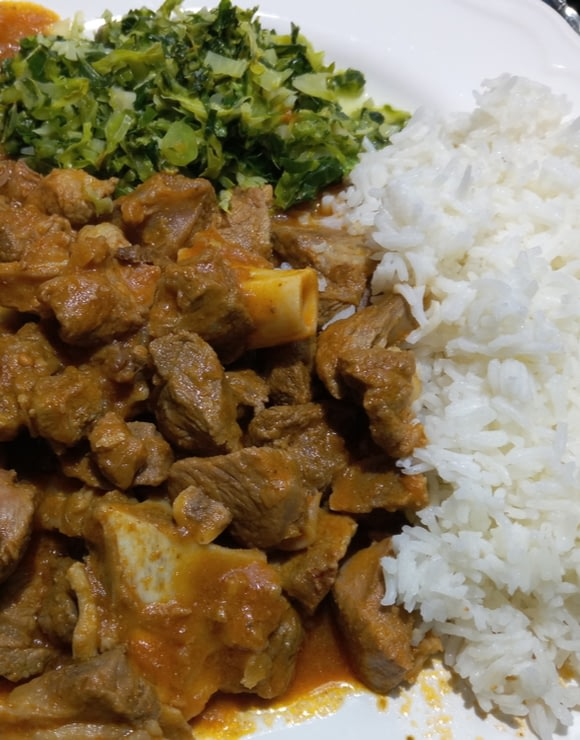 A plate of Kenyan Stews made from meat, potatoes, and vegetables served with ugali