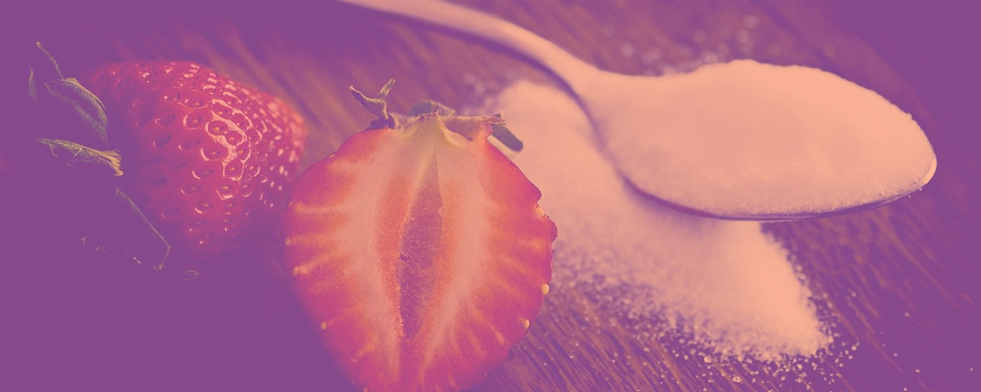 a sliced strawberry next to a spoonful of sugar