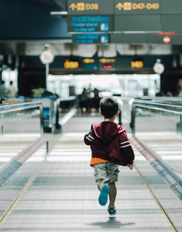 Small boy running through an airport terminal