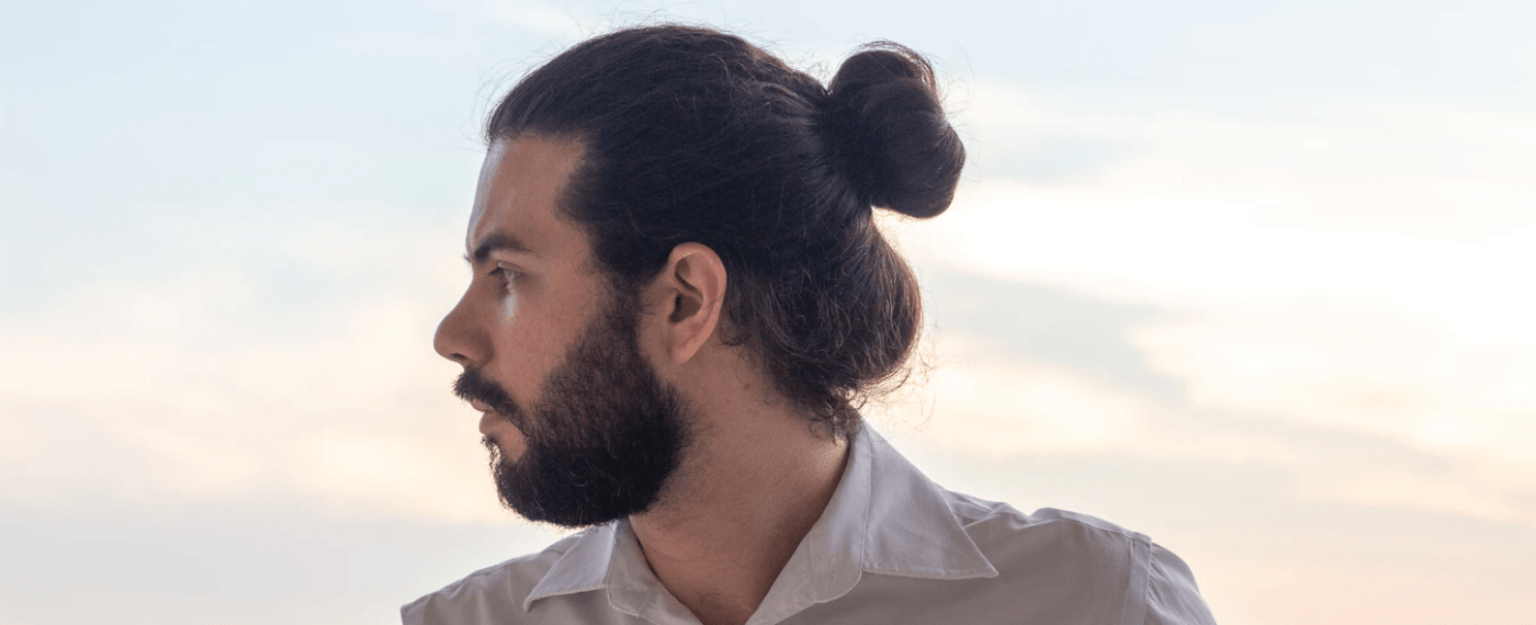 Man with beard and man-bun looking off to the side
