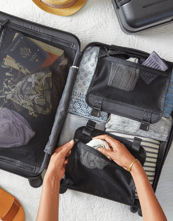Woman neatly packing a travel suitcase for children