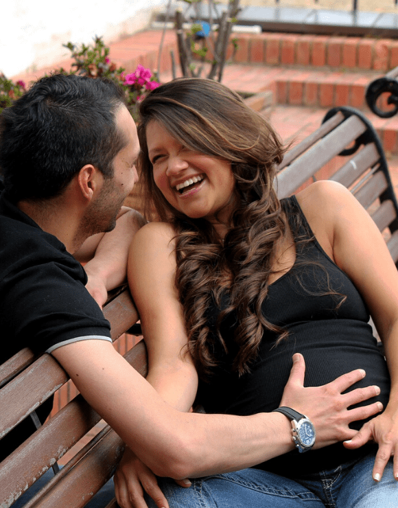 Father smiles with his hand on pregnant wife's stomach