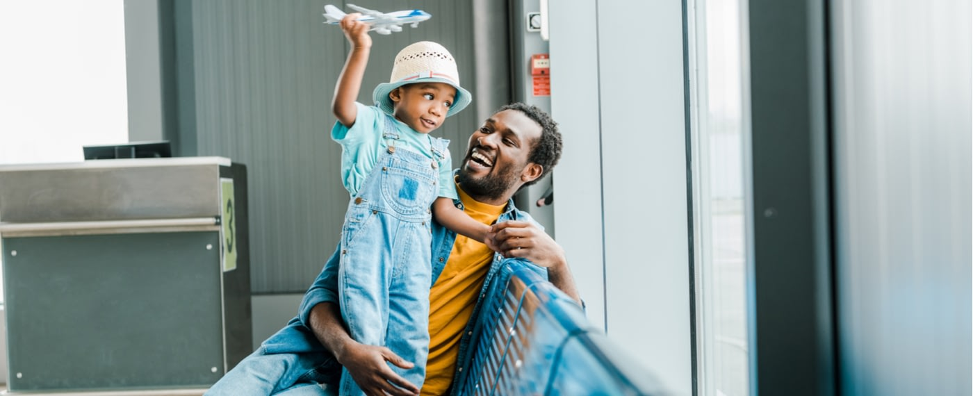 Father holding his son while waiting in airport terminal
