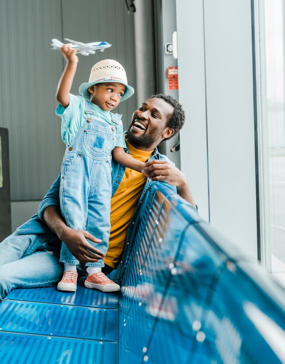 Father watching son play with toy airplane while sitting in airport terminal