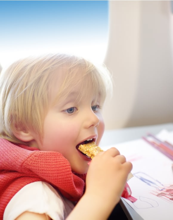Small child enjoying a granola snack while traveling on an airplane