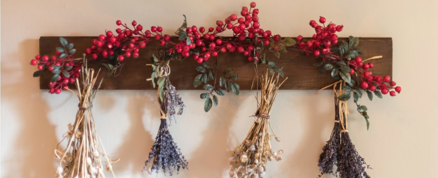 Dried fruit and rose hip hanging from a wooden panel on a wall
