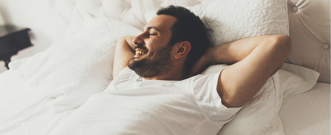 Man lying in bed with arms behind his head and smiling