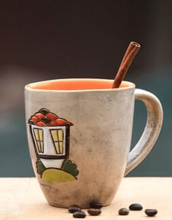 a cup of cinnamon spiced tea with a fresh stick of cinnamon sticking out of the top