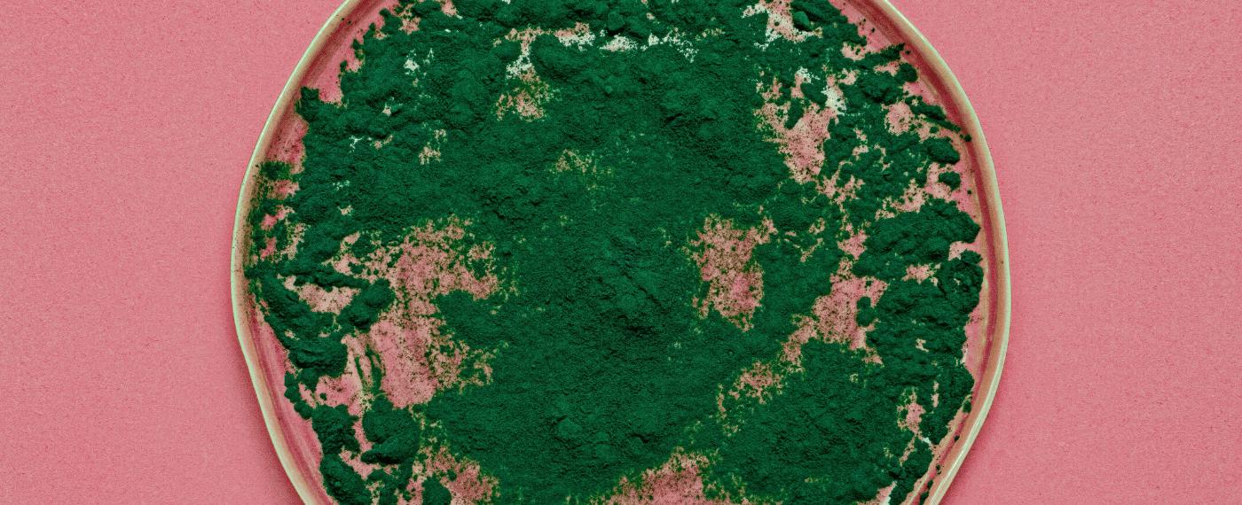 spirulina powder scattered around a round dish