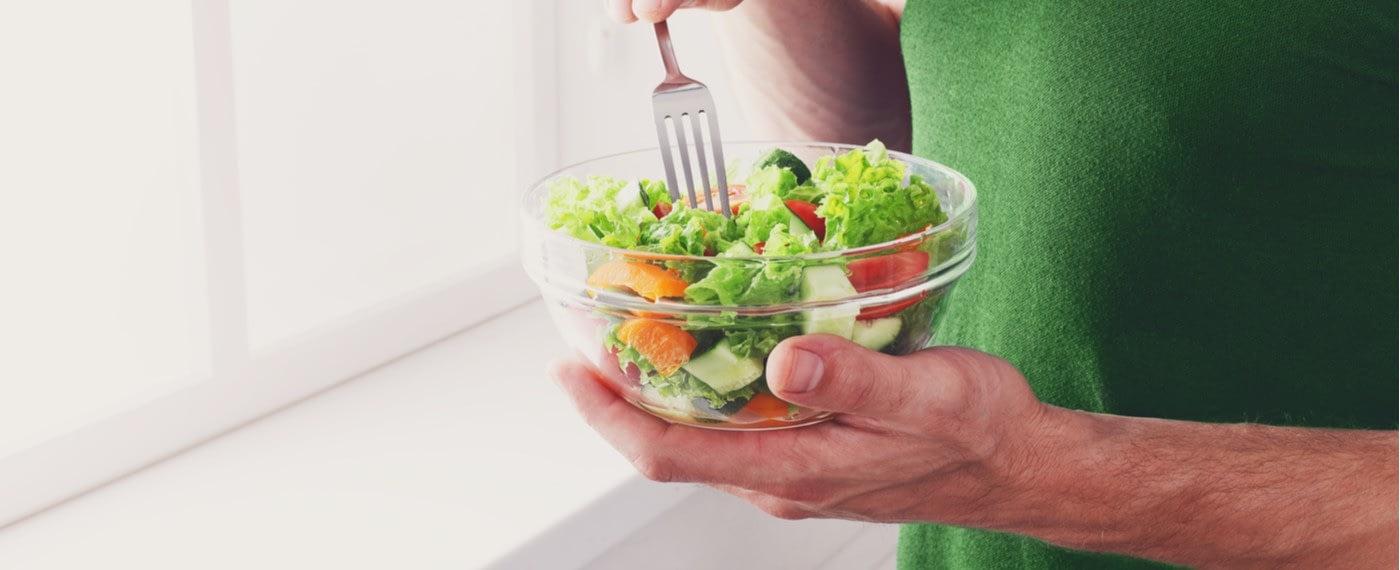 Man eating a bowl of salad