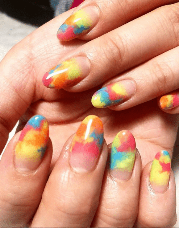 Up close shot of manicured nails with tie-dye nail polish