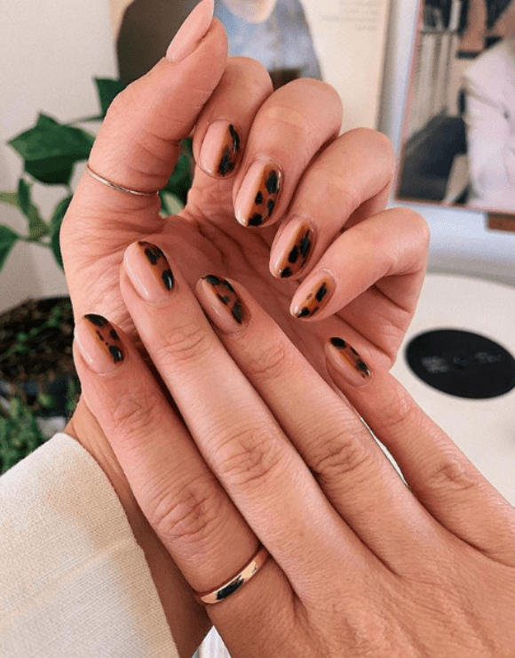 Up close view of manicured nails with leopard nail polish