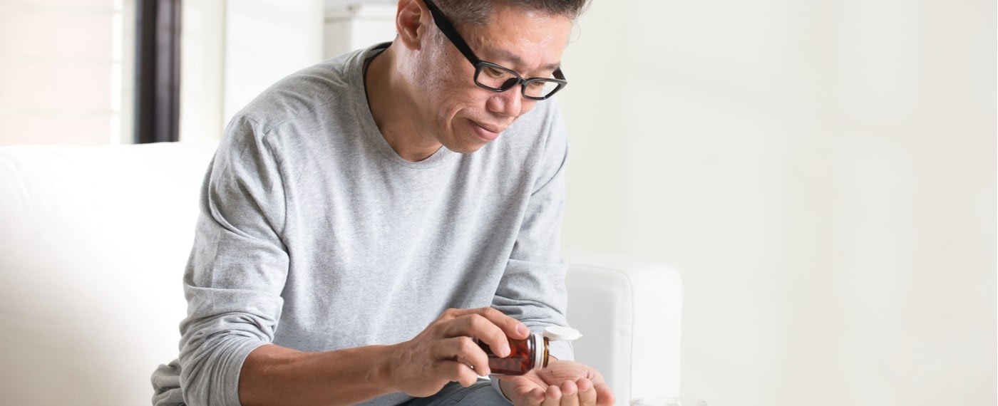 Older male taking traditional oral pain management medication