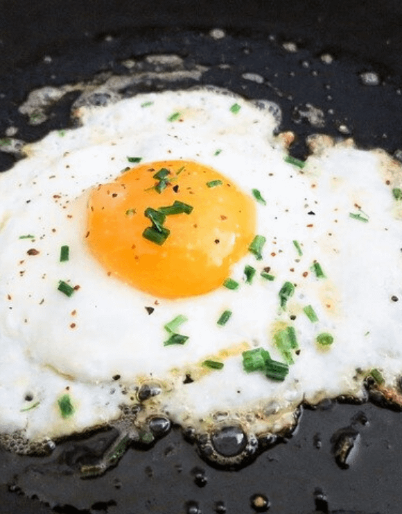 A sizzling fried egg in a pan sprinkled with green onions