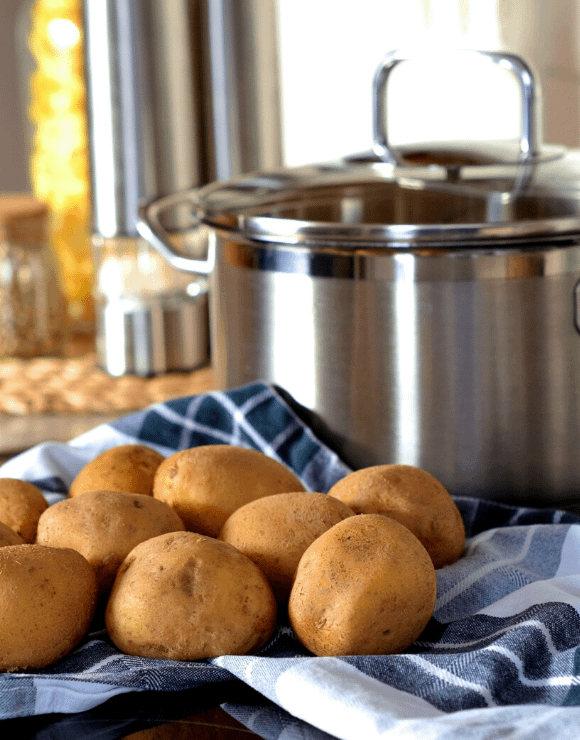 Uncooked potatoes sitting next to a cooking pot