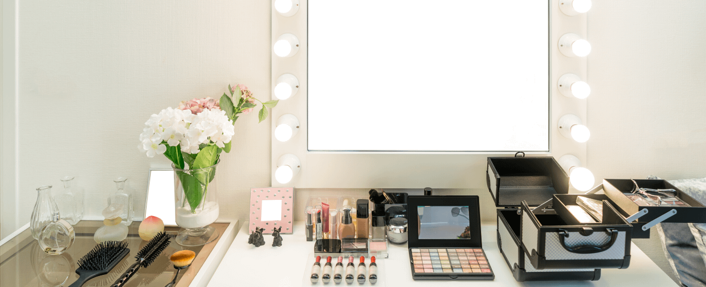 Brightly lit makeup vanity mirror with makeup products spread out