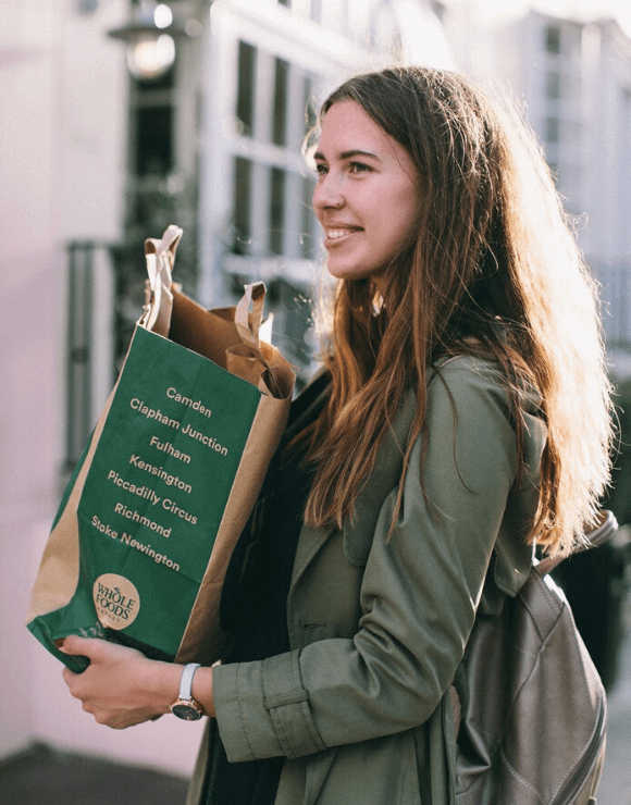 woman smiling while carrying recyclable bag of groceries