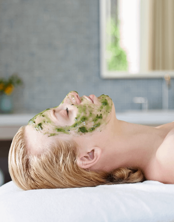 woman lies peacefully on massage table while wearing a CBD infused facial mask