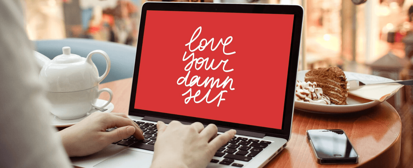 """Woman typing on a laptop screen the words """"Love Your Damn Self"""""""