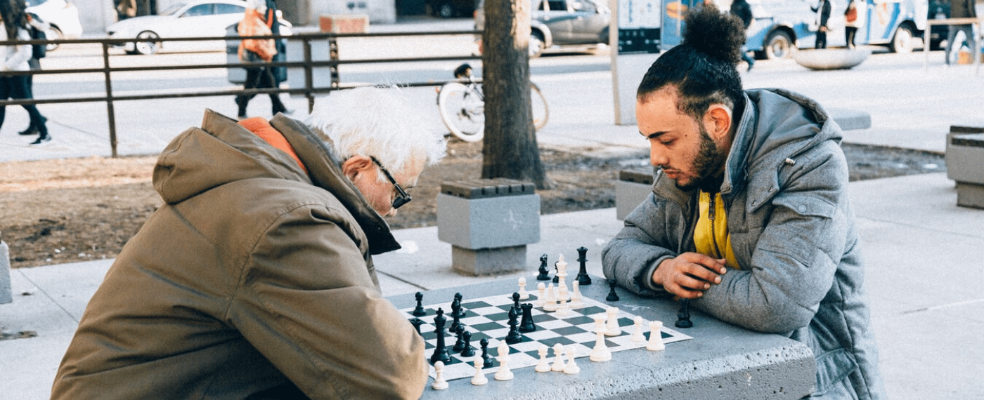 Older man playing chess in the park with a younger male