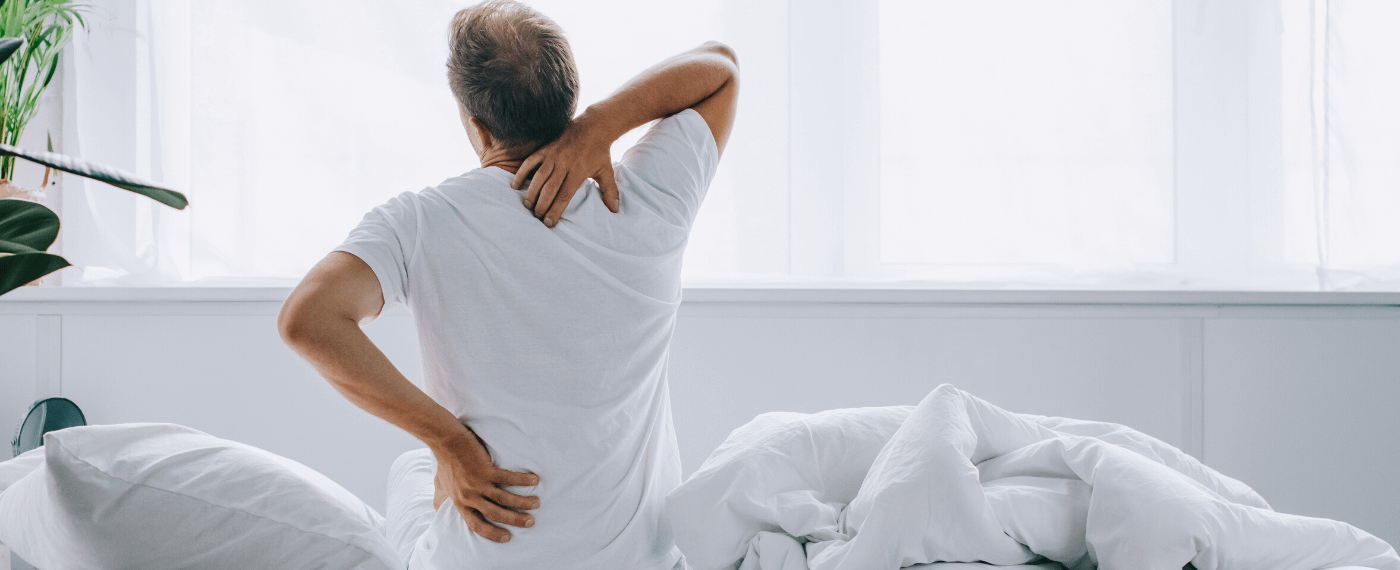 Man waking up fro sleep stretching back in a painful manner