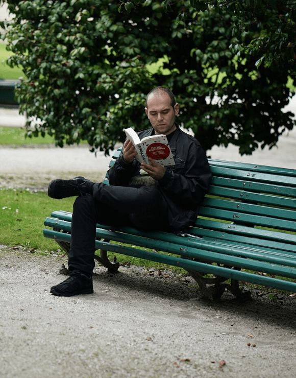 Man reads book on park bench about struggling with self-love