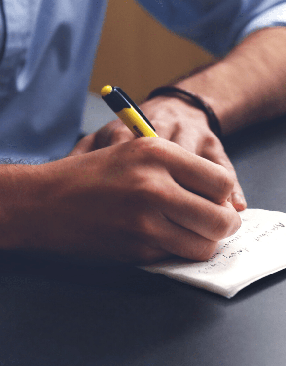 Man writing down self-care ideas